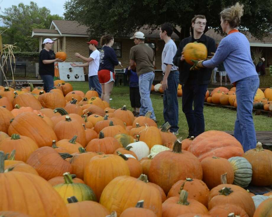 Volunteers from St. Luke's United Methodist Church set up a human transfer line Oct. 8, to get the pumpkins off the truck and into the yard for the annual St. Luke's Pumpkin Patch. Photo by Tim Fischer/Midland Reporter-Telegram Photo: Tim Fischer