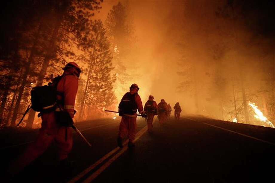 Inmate firefighters walk along state Highway 120 as firefighters continue to battle the Rim Fire near Yosemite National Park, Calif., on Sunday, Aug. 25, 2013. Fire crews are clearing brush and setting sprinklers to protect two groves of giant sequoias as a massive week-old wildfire rages along the remote northwest edge of Yosemite National Park. (AP Photo/Jae C. Hong) Photo: Jae C. Hong / AP2013