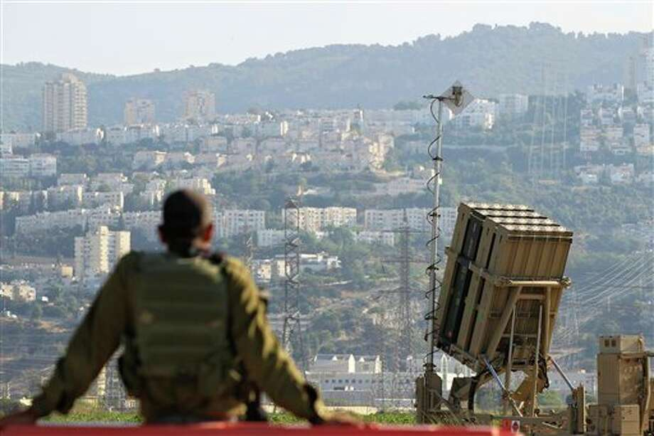 An Israeli soldier is seen next to an Iron Dome rocket interceptor battery deployed near the northern Israeli city of Haifa, Wednesday, Aug. 28, 2013. Israel ordered a special call-up of reserve troops Wednesday as nervous citizens lined up at gas-mask distribution centers, preparing for possible hostilities with Syria. (AP Photo/Tsafrir Abayov) Photo: Tsafrir Abayov / AP