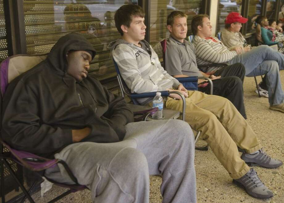 Billy Lee naps Friday morning as the first customer in line at At&T, securing his position around noon on Thursday, as Josh Mercer, Andrew Clifton and others wait for the store to open. Photo by Tim Fischer/Midland Reporter-Telegram Photo: Tim Fischer