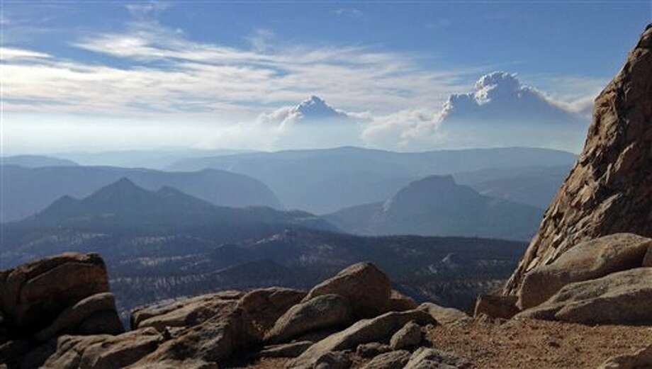 Smoke clouds and bands of haze from the Rim Fire in the western Sierra Nevada loom up some 20 miles behind the famed granite monolith known as Half Dome, right center, seen from 11,500-foot Mt. Clark in Yosemite Valley in Yosemite National Park, Calif., Saturday, Aug. 24, 2013. Crews working to contain one of California's largest-ever wildfires gained some ground Monday against the flames threatening San Francisco's water supply, several towns near Yosemite National Park and historic giant sequoias. Containment of the Rim Fire more than doubled to 15 percent, although it was within a mile of the park's Hetch Hetchy Reservoir, the source of San Francisco's famously pure drinking water, officials said Monday. (AP Photo/Tami Abdollah) Photo: Tami Abdollah / AP2013