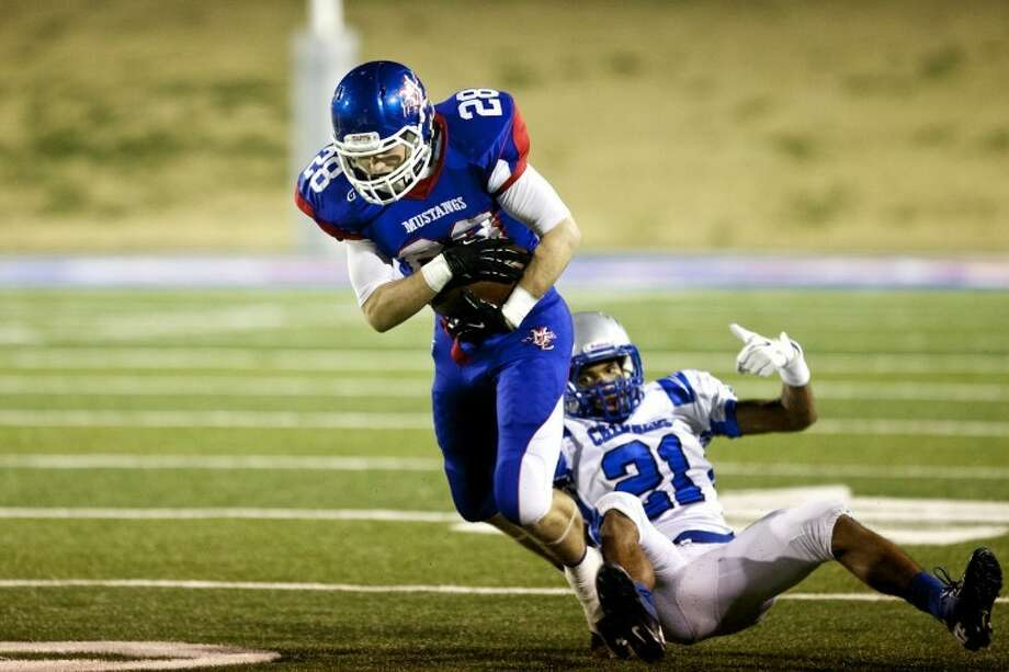Mustang wide reciever Jarrod Koym breaks a tackle by Dallas Christian's Justis Nelson during a TAPPS State Semifinal game at Shotwell Stadium in Abilene Saturday evening. Midland Christian won 48-7. photo by Gary Rhodes Photo: Gary Rhodes