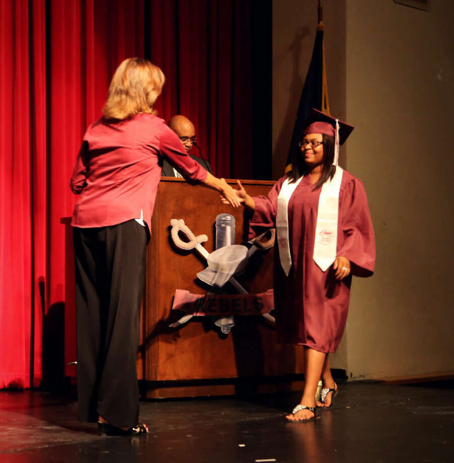 Lee High School Principal Jeanette McNeely awards a diploma to a 2013 summer graduate Monday evening at Lee High School.  Photo: Elizabeth York/Midland ISD