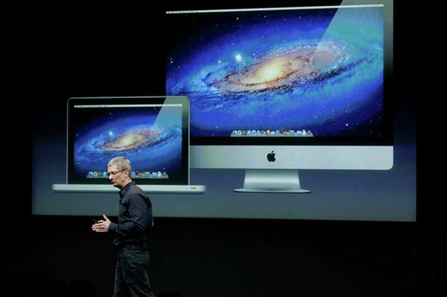 FILE - In this Tuesday, Oct. 4, 2011, file photo, Apple CEO Tim Cook speaks in front of a projection of the Macbook Air and Mac Desktop during announcement at Apple headquarters in Cupertino, Calif. Apple CEO Tim Cook said Thursday the company will produce one of its existing lines of Mac computers in the United States next year. Like most consumer electronics companies, Apple forges agreements with contract manufacturers to assemble its products overseas. (AP Photo/Paul Sakuma, File) Photo: Paul Sakuma / AP