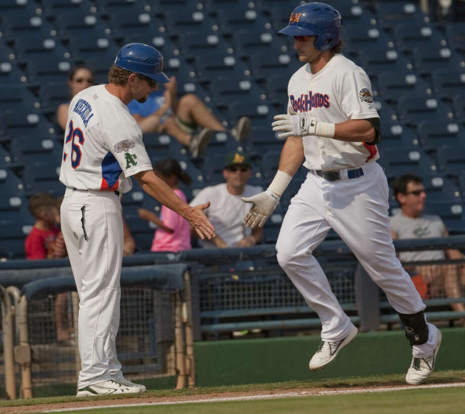 Hounds' manager Aaron Nieckula, left, congratulates Vinnie Catricala as he rounds third on a home run Monday afternoon at CitiBank Ballpark. Tim Fischer\Reporter-Telegram Photo: Tim Fischer