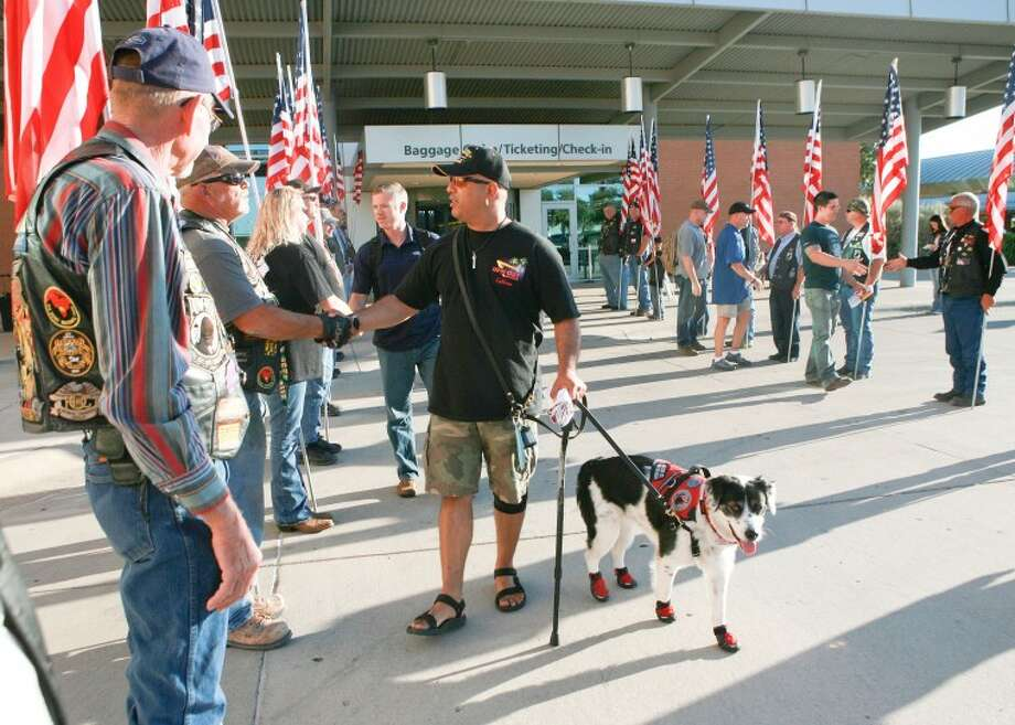 "Ken, a U.S. sergeant first class, and his service dog, ""Bella,"" are welcomed by members of the Patriot Guard Riders Thursday at Midland International Airport. Reel Thanx is providing Ken and five other wounded servicemen with an all-expense-paid fishing trip to Lake Amistad. Cindeka Nealy/Reporter-Telegram Photo: Cindeka Nealy"