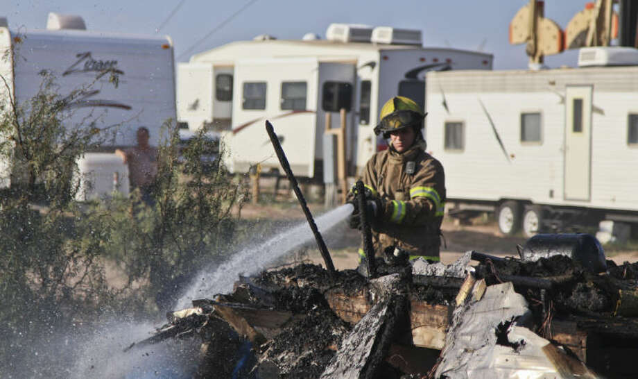 Midland firefighters work to put out a blaze that burned this trailer home down Tuesday in the 5400 block of East County Road 76. Tyler White/Reporter-Telegram Photo: Tyler White