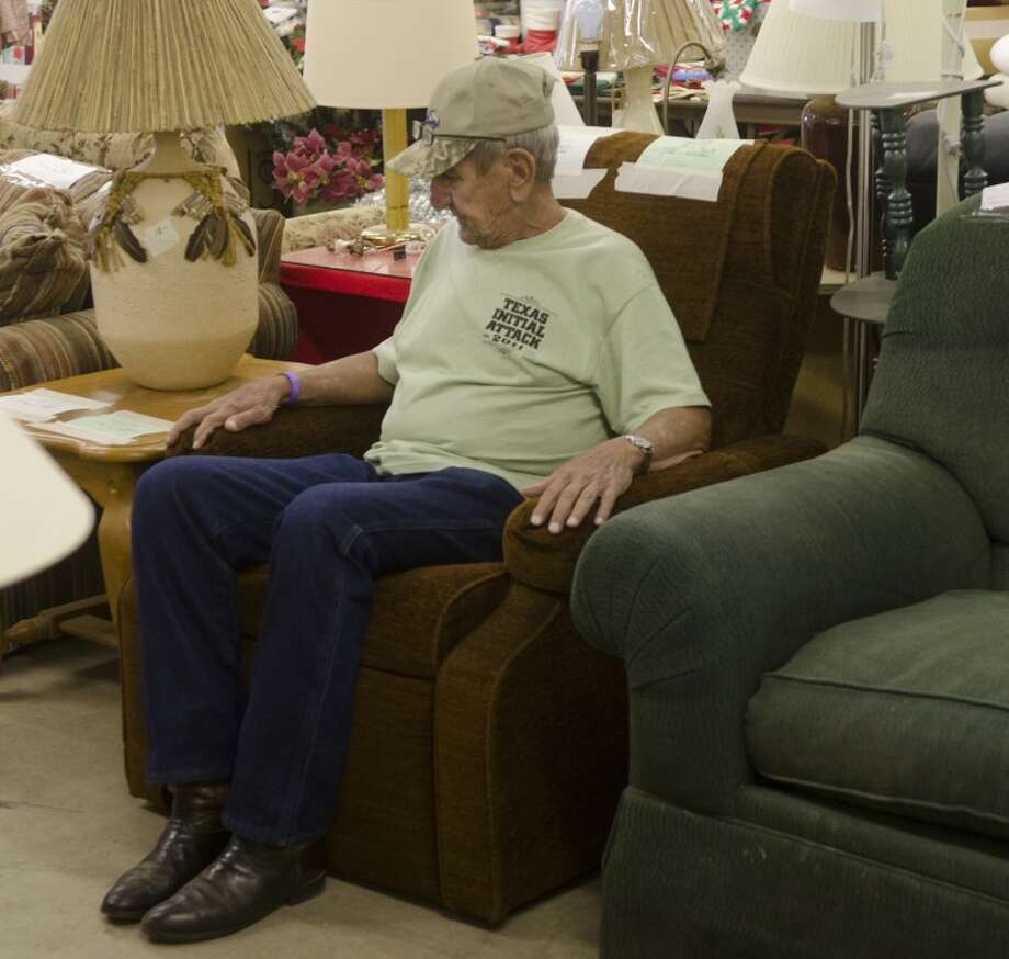 Walter Martin tries out a recliner Friday at the Texas-Size Garage Sale and decides it would be a great addition to his home. Photo: Tim Fischer/Reporter-Telegram