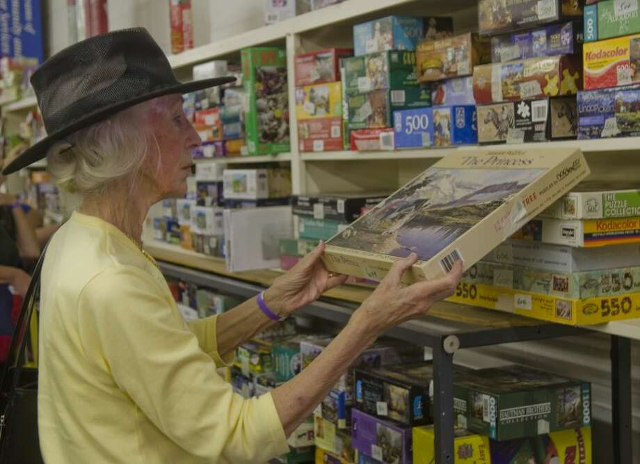 Marian Jones looks at some of the puzzles offered Friday at the Texas-Size Garage Sale to benefit Meals-on-Wheels. Photo: Tim Fischer/Reporter-Telegram