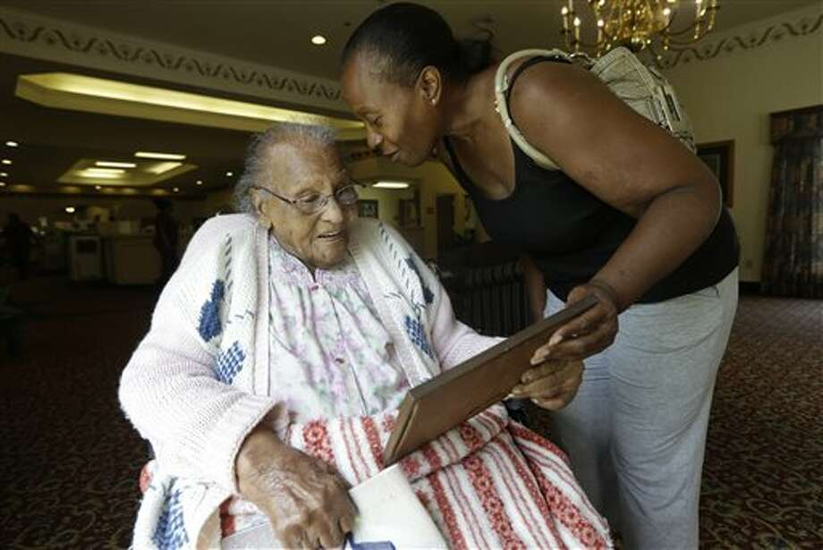 In this Tuesday, July 30, 2013 photo, Jacquelin Finley, right, shows her grandmother Ida Filey, 101, a family photo she recovered during a visit to the house she grew up in with her grandmother in Dirgin, Texas. The Finleys are descendants of slaves holding out against company's attempt to mine East Texas land for coal. (AP Photo/LM Otero) Photo: LM Otero / AP
