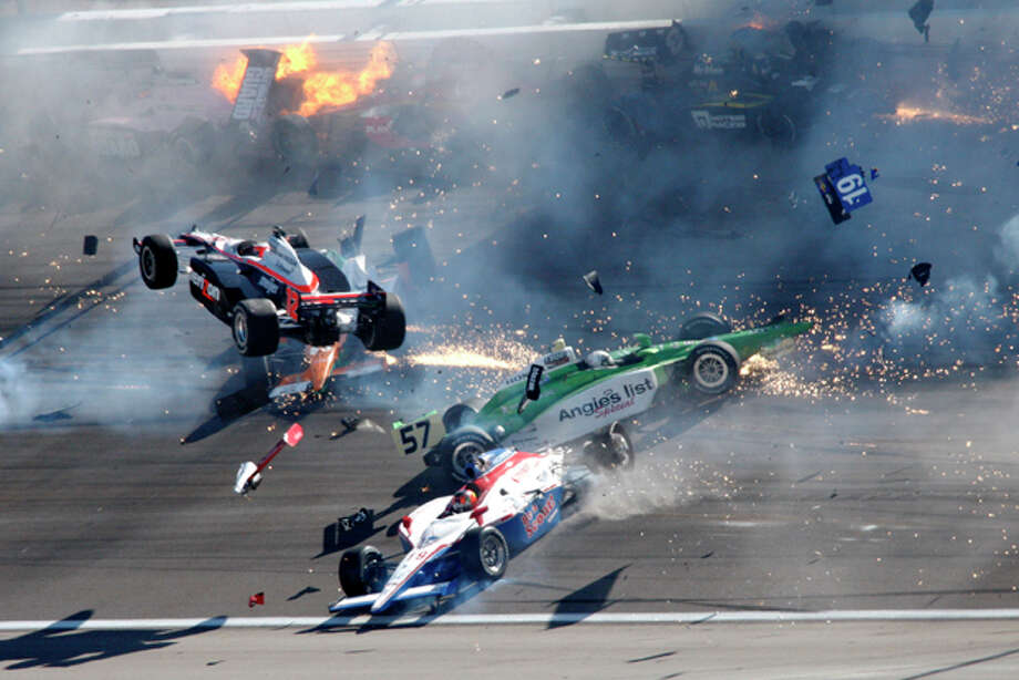 Drivers crash during a wreck that involved 15 cars during the IndyCar Series' Las Vegas Indy 300 auto race at Las Vegas Motor Speedway in Las Vegas on Sunday, Oct. 16, 2011. Will Power (12), of Australia, is airborne at left. Dan Wheldon died following the crash. (AP Photo/Las Vegas Review-Journal, Jessica Ebelhar) Photo: Jessica Ebelhar / Las Vegas Review-Journal