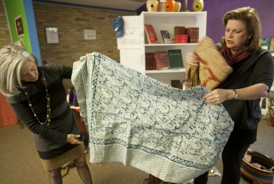 Anne Hover and Bryan Riggs show off some of the hand made designs available during Eternal Threads global bazaar at Holy Trinity Episcopal Church. Tim Fischer\Reporter-Telegram Photo: Tim Fischer
