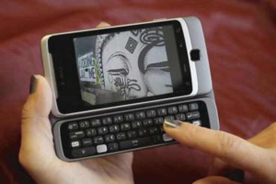 A customer uses a T-Mobile phone. Photo: Eric Risberg / AP