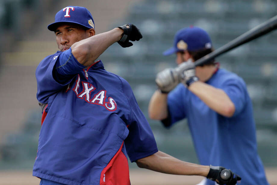 Texas Rangers pitchers Alexi Ogando, left, and C.J. Wilson, right, participate in batting practice Monday, Oct. 17, 2011, in Arlington, Texas. The Rangers and the St. Louis Cardinals are scheduled to play the opening game of baseball's World Series on Wednesday in St. Louis. (AP Photo/Tony Gutierrez) Photo: Tony Gutierrez / AP
