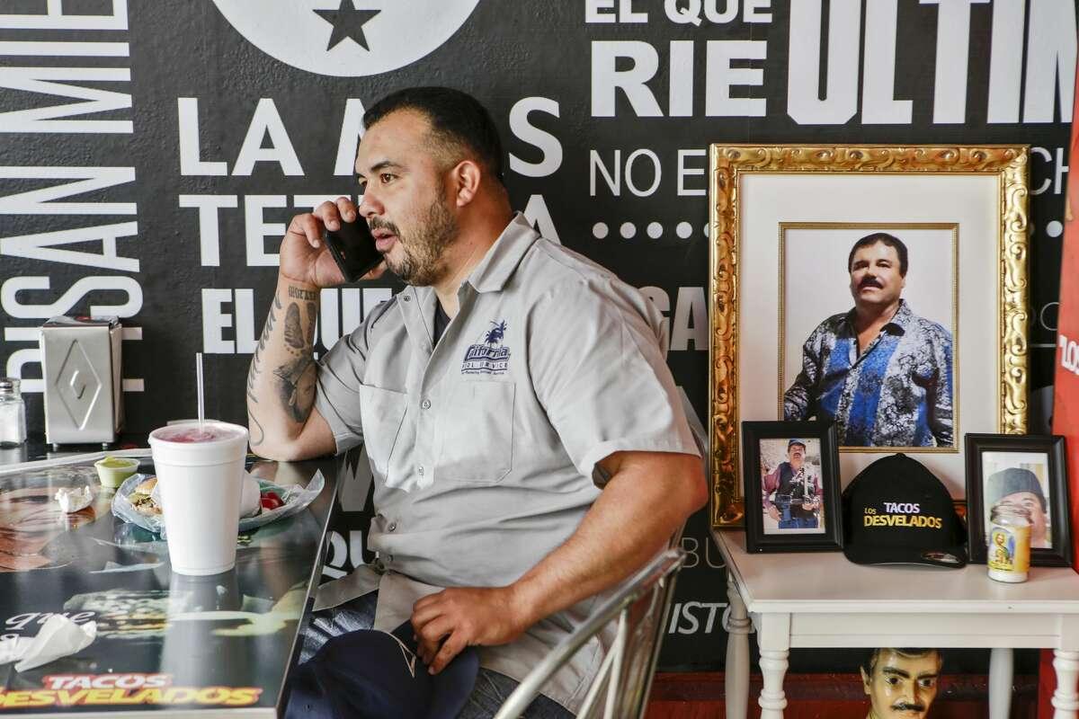 "Marvin Hernandez, 34, eats lunch next to a small table set up in honor of Joaquin ""El Chapo"" Guzman at Tacos Los Desvelados."