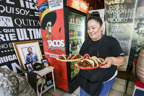 Jackie Gallegos serves at Tacos Los Desvelados, a drug lord-themed taqueria in Maywood, Calif.