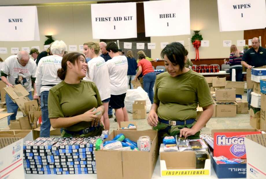 Bianca Flores, left, and Desiree Young, right, of the Lee High Air Force ROTC, volunteer in the assembly line at the Christmas For Our Troops annual packing event Wednesday at First Presbyterian Church. More than 2,000 boxes were packed. James Durbin/Reporter-Telegram Photo: JAMES DURBIN