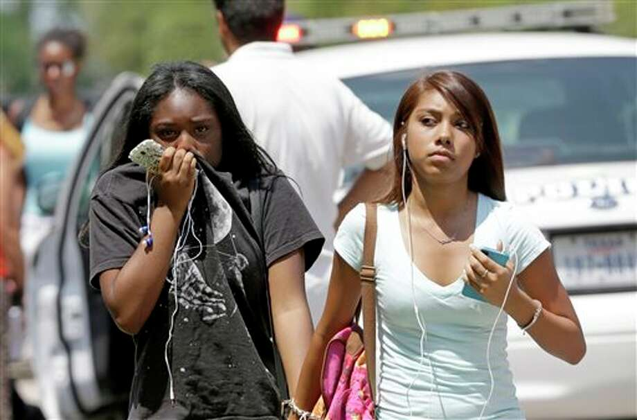 Students walk to their waiting parents outside Spring High School Wednesday, Sept. 4, 2013, in Spring, Texas. The students were dismissed after a 17-year-old student was stabbed to death and three others are injured after a fight at the Houston-area high school. (AP Photo/David J. Phillip) Photo: David J. Phillip / AP