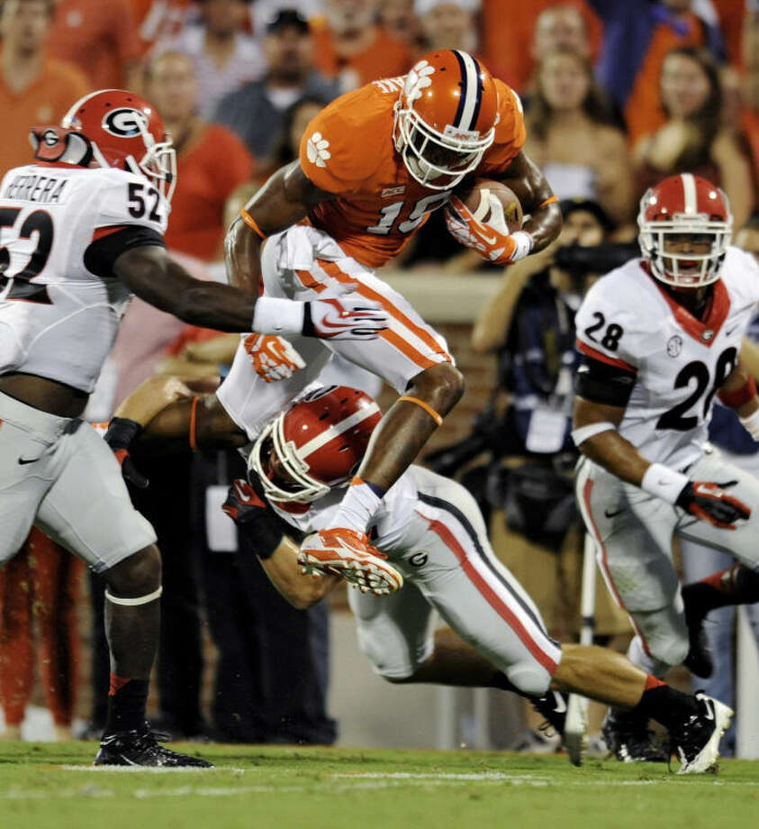 Clemson's Charone Peake leaps through the tackle of Georgia's Connor Norman, bottom, while being pursued by Amarlo Herrera at Memorial Stadium on Saturday in Clemson, S.C. (AP Photo/Richard Shiro) Photo: Richard Shiro