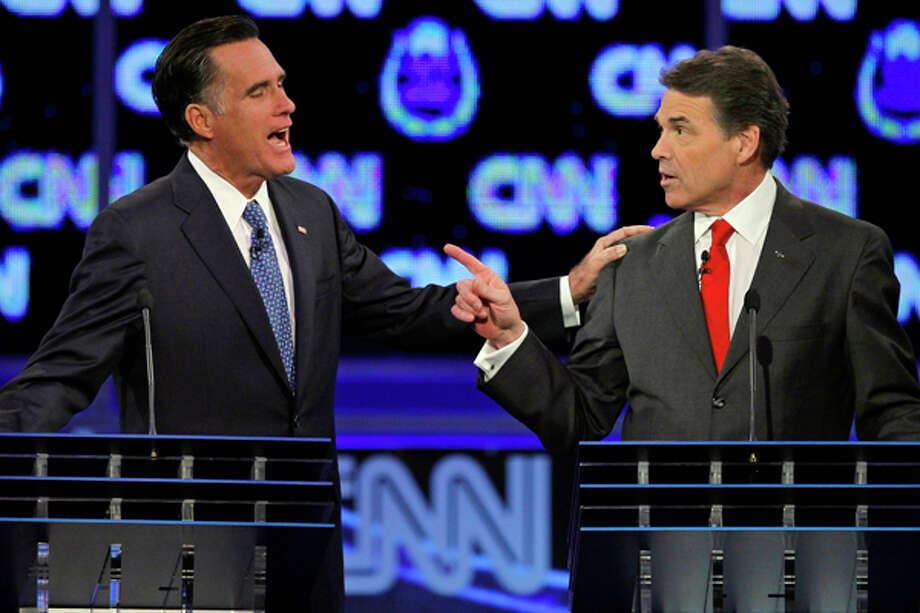 Republican presidential candidates former Massachusetts Gov. Mitt Romney, left, and Texas Gov. Rick Perry speak during a Republican presidential debate Tuesday, Oct. 18, 2011, in Las Vegas. (AP Photo/Chris Carlson) Photo: Chris Carlson / A