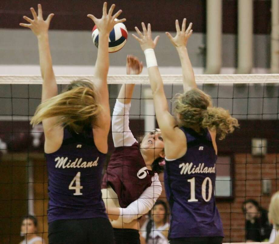 Midland High's Riley Downing (4) and Leigh Collyer (10) attempt to block a spike by Lee's Ciara Sheppard (6) on Tuesday at Lee High School. Photo: Cindeka Nealy