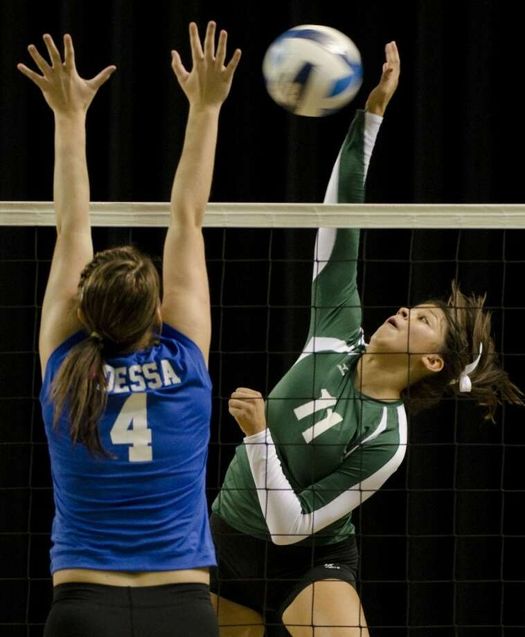 Midland College's Britany Serrano spikes the ball as Odessa College's Laura Reigh attempts to block Wednesday evening at the Chaparral Center. Photo by Tim Fischer/Midland Reporter-Telegram Photo: Tim Fischer