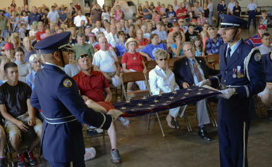 Mdland High Air Force JROTC members, Cadet Lt. Col. Adrian Carrasco and Cadet Col. Robert Prado III demonstrate the steps in folding the American Flag Monday during the Memorial Day Ceremony at the CAF. Tim Fischer\Reporter-Telegram Photo: Tim Fischer