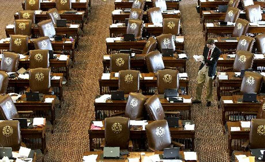 A member of the Sergeant at Arms, Jack Adams, places updated resolutions on the empty desks of House Representatives at the State Capitol on Sunday in Austin. Members of the House of Representatives left the chamber to gather in their respective caucuses before returning to continue the 83rd Legislature. Photo: Associated Press