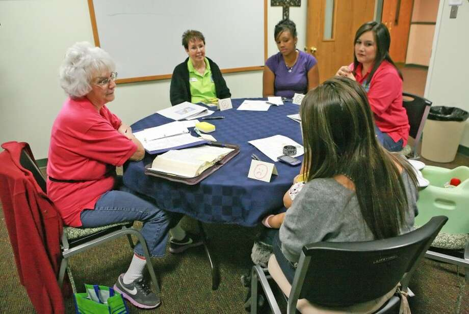 Tier II instructor Sandra Rybicki, from left, and mentors Georgia Davidson, Sadie Marshall and Traci Pequeno talk to a 16-year-old mother caring for her daughter Tuesday during M.A.R.Y. Ministries at First Baptist Church. Cindeka Nealy/Reporter-Telegram Photo: Cindeka Nealy