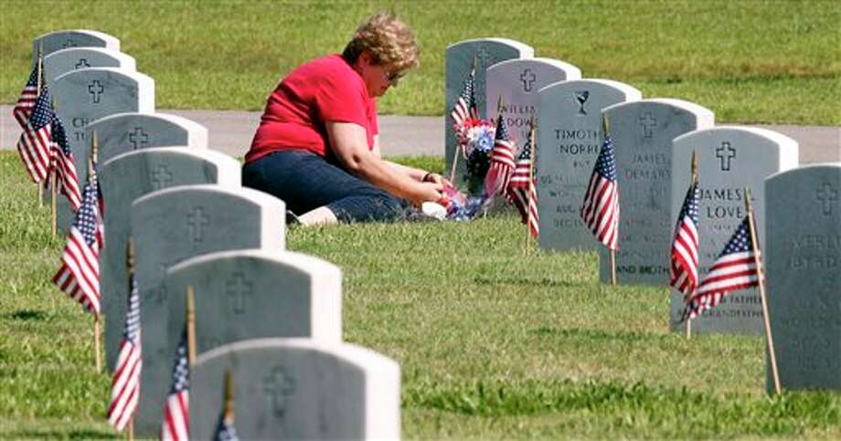 Jeanne McDowell places flowers at the grave of William D. McDowell Sr. after Memorial Day observance at the National Cemetery in Biloxi, Miss. (AP Photo/The Sun Herald, Tim Isbell) TV OUT; MANDATORY CREDIT: MISSISSIPPI PRESS OUT; LOCAL TV OUT WLOX, LOCAL ONLINE OUT; GULFLIVE.COM OUT Photo: Tim Isbell / The Sun Herald