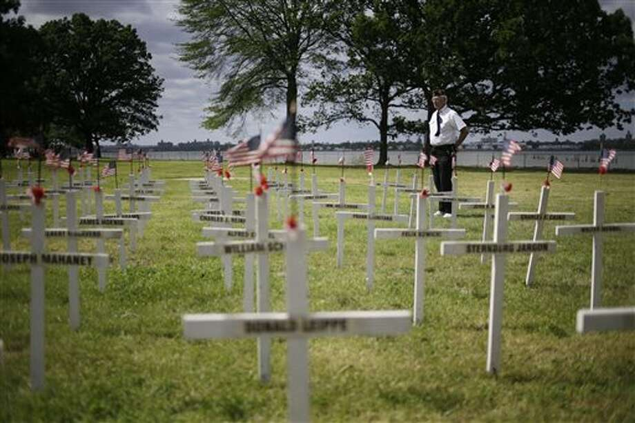 Bob Lewis looks over a field of crosses with names while participating in the College Point Memorial Day Parade in New York, Sunday, May 26, 2013. Lewis made the crosses, 137, for all the service members from College Point that were killed from the Civil War to the Vietnam War. (AP Photo/Seth Wenig) Photo: Seth Wenig / AP2013