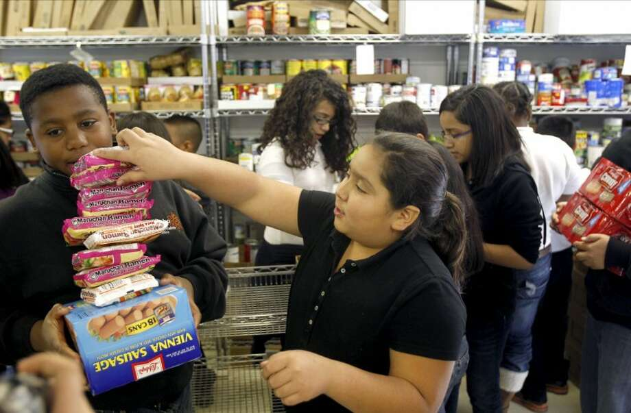 Pease Elementary student council members carry canned goods into the Memorial Food Pantry Thursday in Midland. The students of Pease Elementary collected 4,491 cans. James Durbin/Reporter-Telegram Photo: JAMES DURBIN