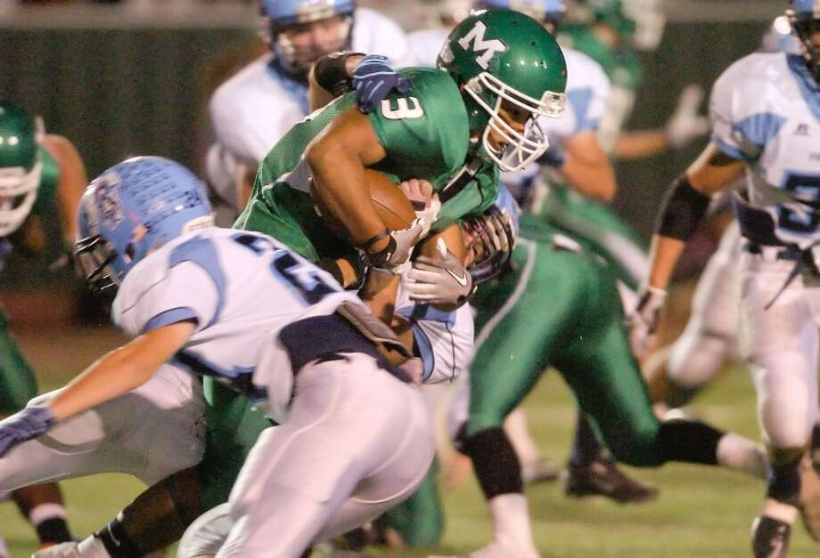 Greenwood's Kyle Rimer (24) and Jacob Armitage (10) tackle Monahans running back Pedro Cano (13) Friday during their game at Memorial Stadium in Monahans. Cindeka Nealy/Reporter-Telegram Photo: Cindeka Nealy