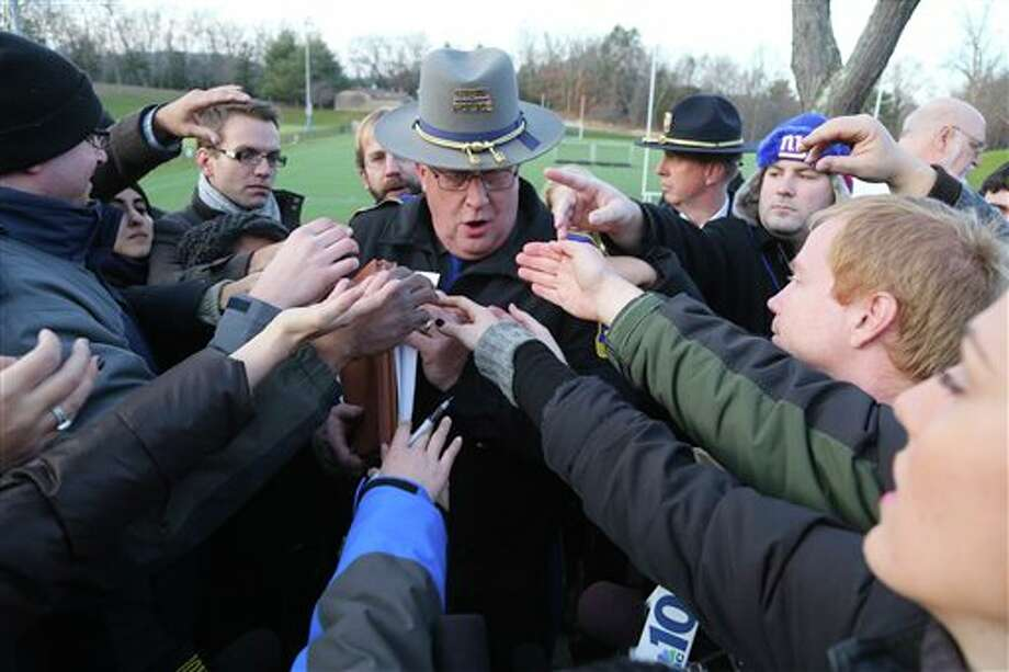 "Lt. J. Paul Vance of the Connecticut State Police is surrounded by reporters as he hands out the list of victims of the shooting at the Sandy Hook Elementary School, Saturday, Dec. 15, 2012 in Sandy Hook village of Newtown, Conn. The victims of the shooting were shot multiple times by semiautomatic rifle, according to Connecticut Chief Medical Examiner H. Wayne Carver II, M.D. Carver called the injuries ""devastating"" and the worst he and colleagues had ever seen. Police began releasing the identities of the dead. All of the 20 children killed were 6 or 7 years old. Carver, said he examined seven of the children killed, and two had been shot at close range. When asked how many bullets were fired, he said, ""I'm lucky if I can tell you how many I found."" (AP Photo/Mary Altaffer) Photo: Mary Altaffer / AP2012"