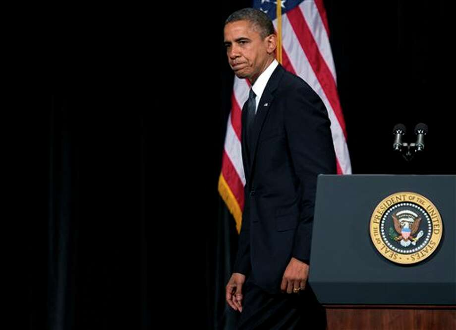 President Barack Obama walks off stage after delivering a speech at an interfaith vigil for the victims of the Sandy Hook Elementary School shooting on Sunday, Dec. 16, 2012 at Newtown High School in Newtown, Conn. A gunman walked into Sandy Hook Elementary School on Friday and opened fire, killing 26 people, including 20 children. (AP Photo/Evan Vucci) Photo: Evan Vucci / 2012 AP