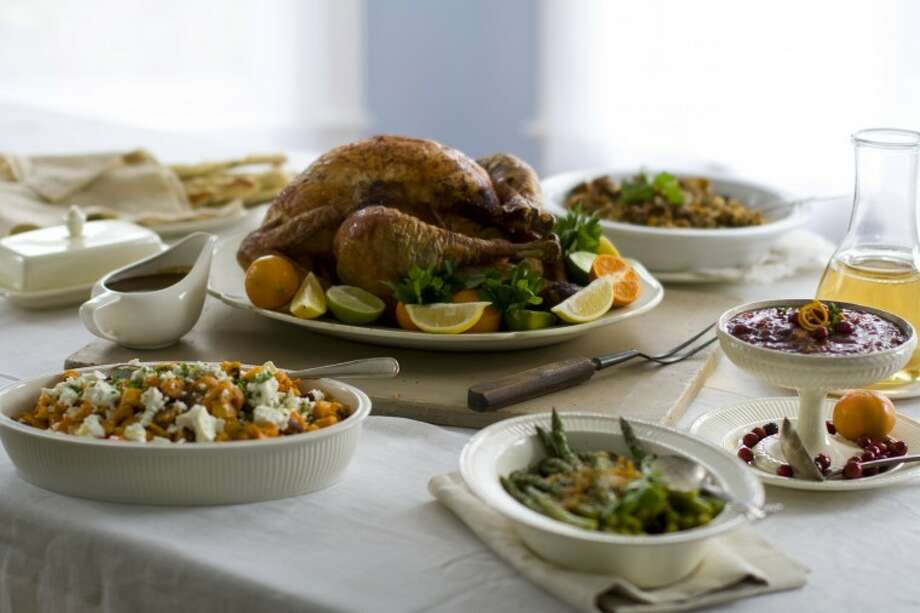This Oct. 13, 2011 photo shows a citrus turkey surrounded by side dishes in Concord, N.H. Big holiday meals can be a hodgepodge of unrelated flavors, textures and sensations. The challenge for the host is to tie it all together. (AP Photo/Matthew Mead) Photo: Matthew Mead/AP