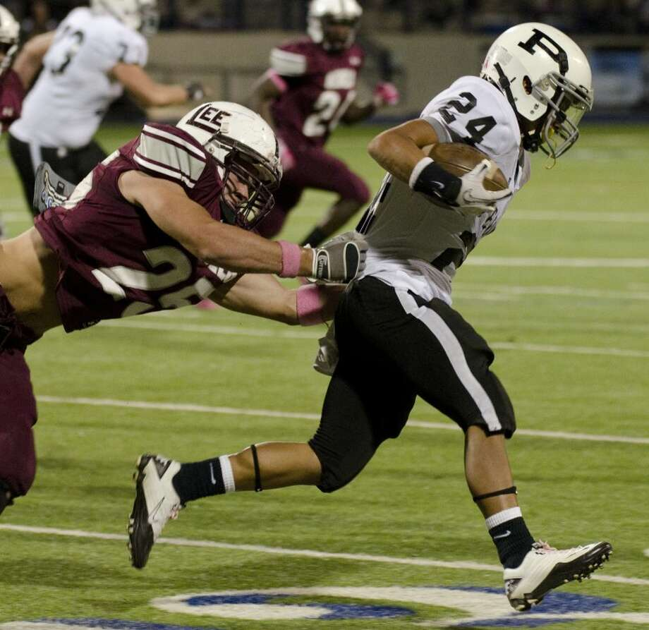 Lee High's Luke Stice holds on to Permian's Andrew Perez shirt to bring him down Friday night at Grande Communications Stadium. Photo by Tim Fischer/Midland Reporter-Telegram Photo: Tim Fischer