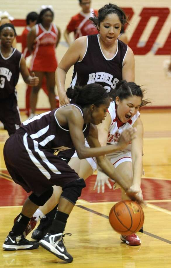 Midland Lee's Daija Stanford (10) tries to get the ball from Odessa High's Kali Cobos (2) during their district basketball game Friday at the Odessa High Fieldhouse. Also pictured is Lee's Jackie Rivas (22). Photo: Mark Sterkel|Odessa American
