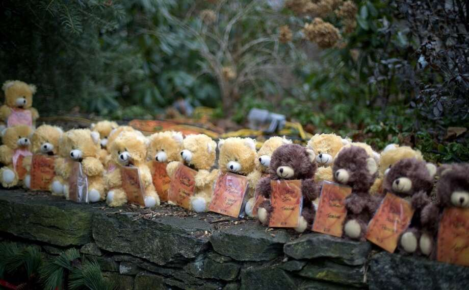Teddy bears, each representing a victim of the Sandy Hook Elementary School shooting, sit on a wall at a sidewalk memorial, Sunday, Dec. 16, 2012, in Newtown, Conn. A gunman walked into Sandy Hook Elementary School in Newtown Friday and opened fire, killing 26 people, including 20 children. (AP Photo/David Goldman) Photo: David Goldman