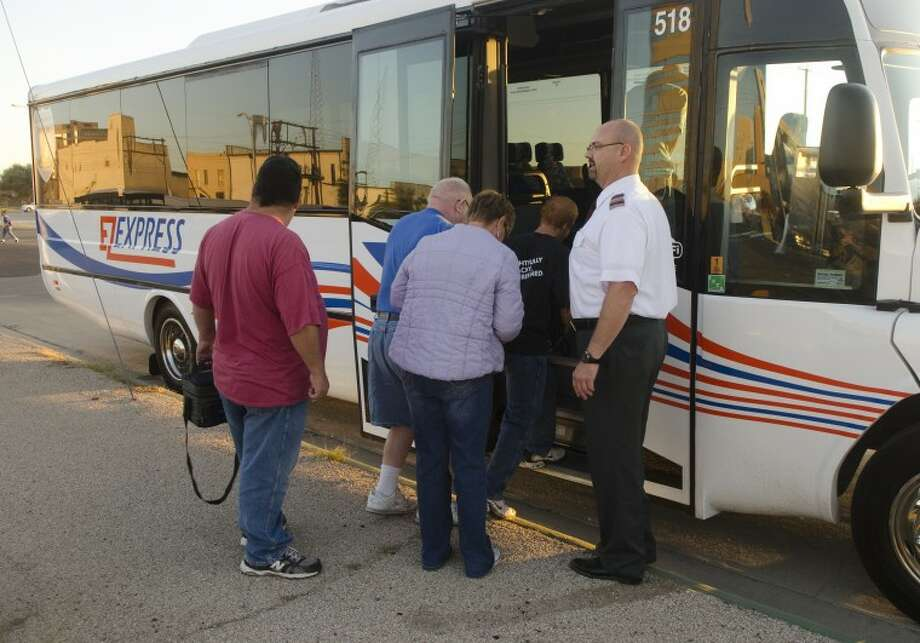 EzRider driver Jason Phillips, right, welcomes passengers Monday morning on the new EzExpress bus with direct transportation between Midland and Odessa. Photo by Tim Fischer/Midland Reporter-Telegram Photo: Tim Fischer