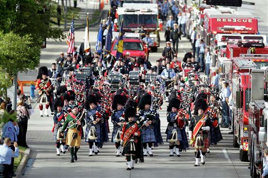 Bagpipers lead firefighters and others in march to a memorial service honoring four Houston firefighters at Reliant Stadium, Wednesday, June 5, 2013 in Houston. Dozens of fire trucks and emergency services vehicles from New Orleans, Dallas and elsewhere formed a long procession on flag-lined streets leading to the stadium. Killed in the fire when the motel structure collapsed were Capt. Matthew Renaud, 35, engineer operator Robert Bebee, 41, firefighter Robert Garner, 29, and Anne Sullivan, 24, a probationary firefighter who had graduated in April from the Houston Fire Department Academy. (AP Photo/Houston Chronicle, Melissa Phillip) MANDATORY CREDIT Photo: Melissa Phillip / Houston Chronicle