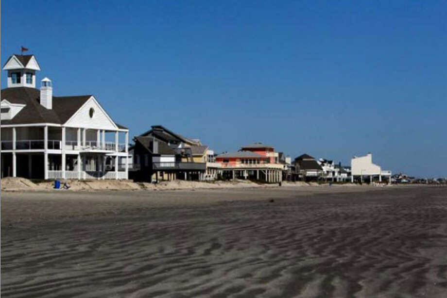 Homes sit along Pirates Beach on Galveston's West End about five miles from the city's protective seawall Wednesday, Oct. 19, 2011. A new book published by Rice University about Galveston Island questions whether anyone should live on its western end, a subject of increasing debate on the island. The book recommends that all of the human habitation be pulled back behind the sea wall. Photo: ( Johnny Hanson / Houston Chronicle )