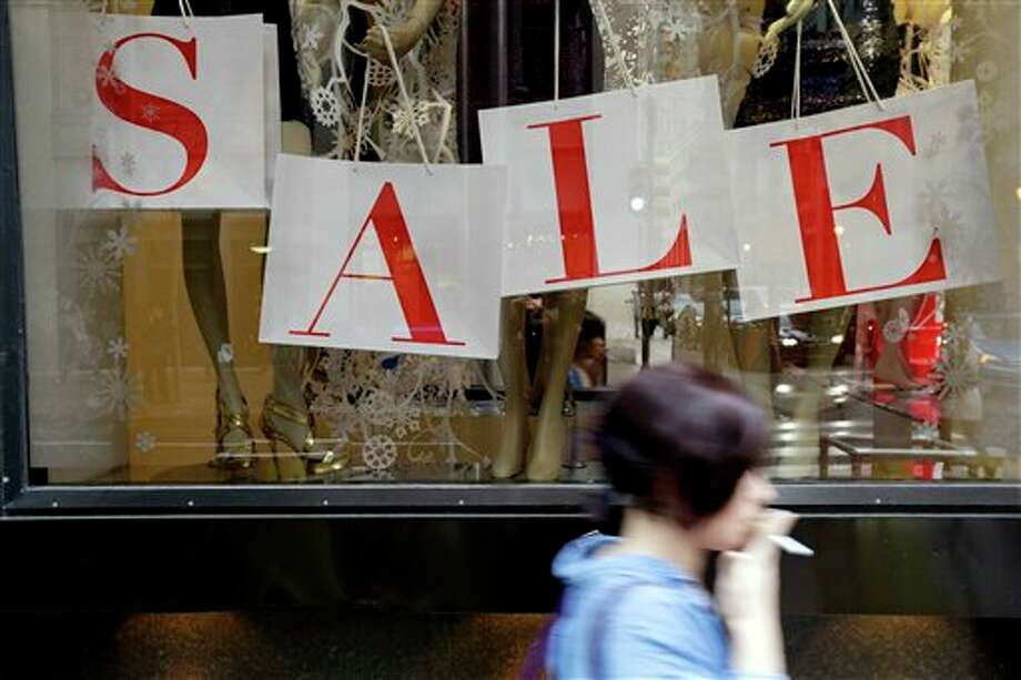 "In this Tuesday, Dec. 18, 2012, photo, a person passes a retail store with sale sign displayed in the window in Philadelphia. When it comes to big discounts, better late than never. This holiday shopping season, stores haven't been offering the same big discounts as they did in previous years as they tried to lure shoppers in with other incentives,but during the final days leading up to Christmas, shoppers will see more of those jaw-dropping ""70 percent off"" sale signs as stores try to salvage a season that so far has been disappointing. (AP Photo/Matt Rourke) Photo: Matt Rourke / AP"