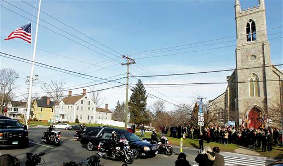 While mourners gather outside of Trinity Episcopal Church, right, during funeral services for Benjamin Andrew Wheeler, one of the students killed in the Sandy Hook Elementary School shooting last week, a hearse with another shooting victim rides through during a procession, Thursday, Dec. 20, 2012, in Newtown, Conn. The victims died when the gunman, Adam Lanza, walked into Sandy Hook Elementary School in Newtown, Dec. 14, and opened fire, killing 26 people, including 20 children, before killing himself. (AP Photo/Julio Cortez) Photo: Julio Cortez / AP