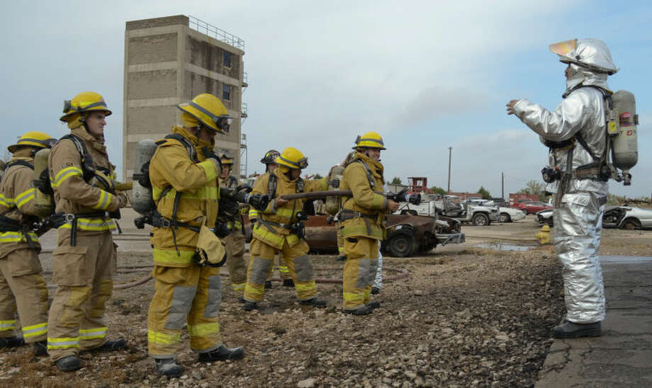 Fire Capt. James Larry talks to new hire firefighters as they train on putting out a flammable liquid fire, diesel, Friday at the Harris Field training center. Tim Fischer\Reporter-Telegram Photo: Tim Fischer