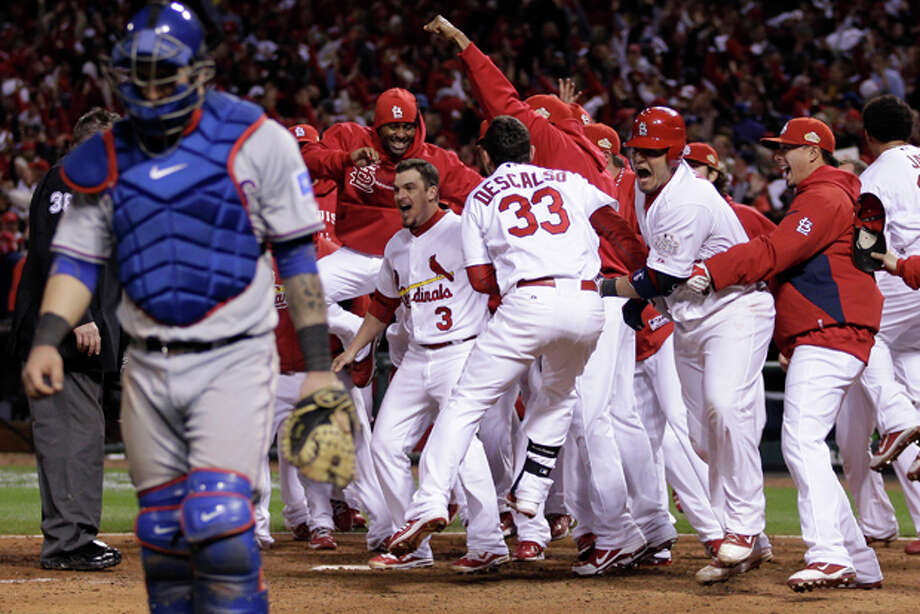 Texas Rangers catcher Mike Napoli walks away as the St. Louis Cardinals celebrate after David Freese hit a walk-off home run during the 11th inning of Game 6 of baseball's World Series Thursday, Oct. 27, 2011, in St. Louis. (AP Photo/Matt Slocum) Photo: Matt Slocum / AP