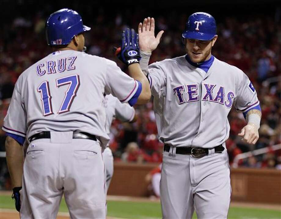 Texas Rangers' Josh Hamilton is congratulated by Nelson Cruz (17) after scoring a run during the first inning of Game 7 of baseball's World Series against the St. Louis Cardinals Friday, Oct. 28, 2011, in St. Louis. (AP Photo/Matt Slocum) Photo: Matt Slocum / AP