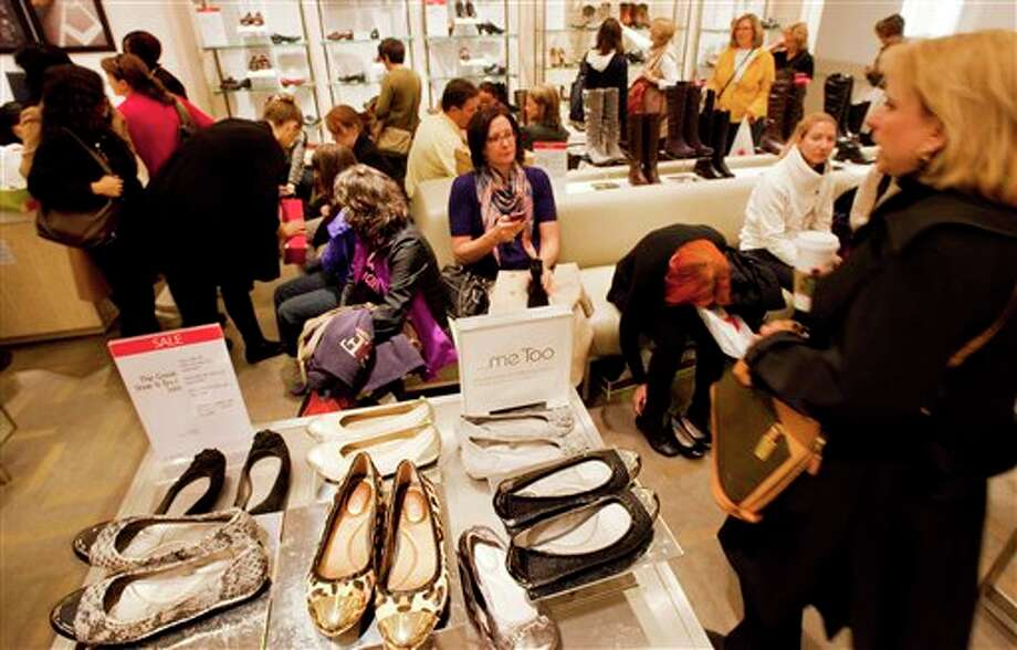 In this photo of Friday, Oct. 12, 2012, customers shop at Macy's shoe department in New York. Shoes are coming out of the closet and landing under the Christmas tree. They're a top seller this holiday season _ a big feat considering they don't usually make peoples' gift lists. (AP Photo/Mark Lennihan) Photo: Mark Lennihan / AP2012