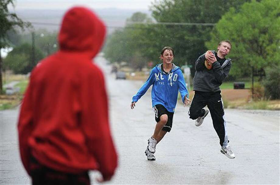 D.J. Koch, from left, Dylan Carr, both 16, and Colin Weaver, 15, play football as the rain falls in Rotan earlier this month. (AP Photo/The Abilene Reporter-News, Victor Cristales) Photo: VICTOR CRISTALES / ABILENE REPORTER-NEWS