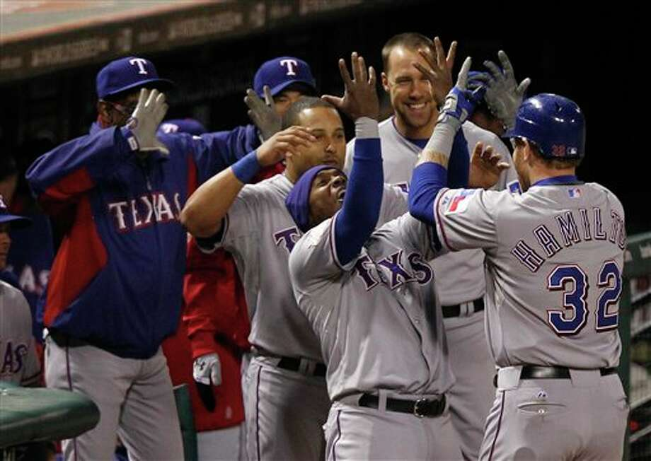 Texas Rangers' Josh Hamilton is congratulated by Esteban German (6) after Hamilton hit a two-run home run during the 10th inning of Game 6 of baseball's World Series against the St. Louis Cardinals Thursday, Oct. 27, 2011, in St. Louis. (AP Photo/Eric Gay) Photo: Eric Gay / AP